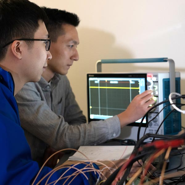 Rice graduate students Joshua Chen, left, and Zhanghao Yu test a prototype neural implant that can be programmed and charged remotely with a magnetic field.